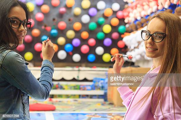 Friends shooting with darts on multicolored ballon