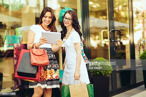 Friends shopping and using a tablet in the city