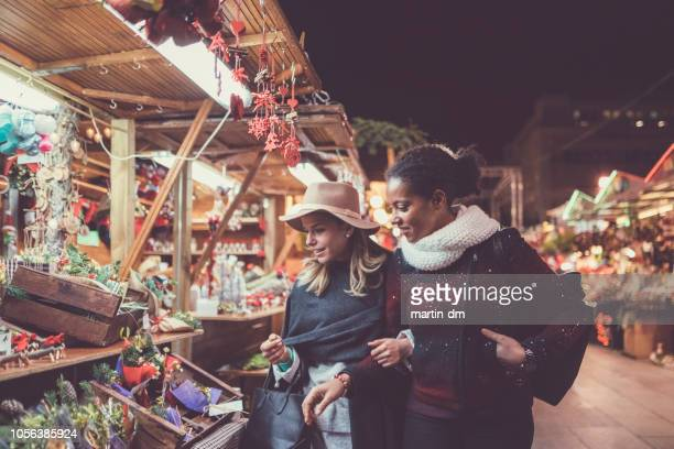 friends shopping christmas presents - christmas market stock pictures, royalty-free photos & images