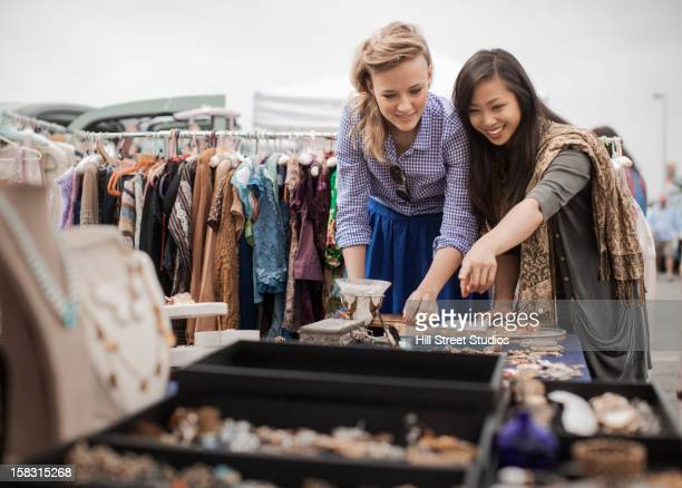friends shopping for jewelry in flea market - jewellery products stock photos and pictures