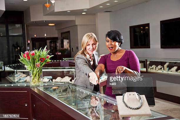 friends shopping together in jewelry store - jewelry store stock pictures, royalty-free photos & images
