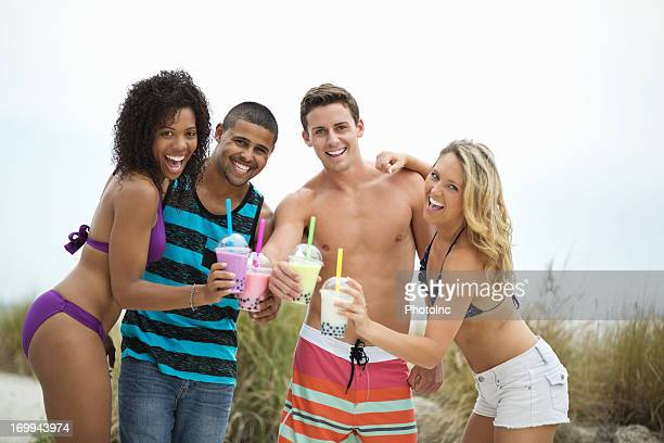 Friends Showing Bubble Tea Together At Beach