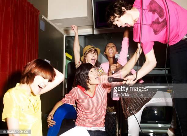 Friends singing in karaoke club