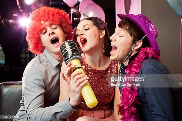 friends singing karaoke in fancy dress. - big mike stock pictures, royalty-free photos & images