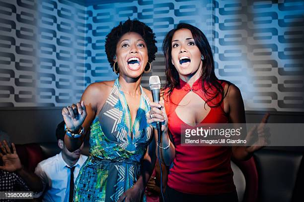 friends singing karaoke in nightclub - duet stock pictures, royalty-free photos & images