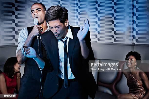 friends singing karaoke in nightclub - club singer fotografías e imágenes de stock