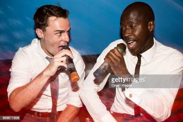 friends singing karaoke in nightclub - karaoke stock pictures, royalty-free photos & images