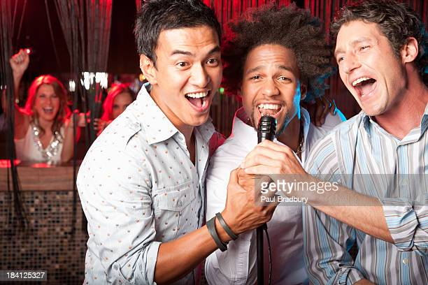 friends singing out at a club - karaoke stock pictures, royalty-free photos & images