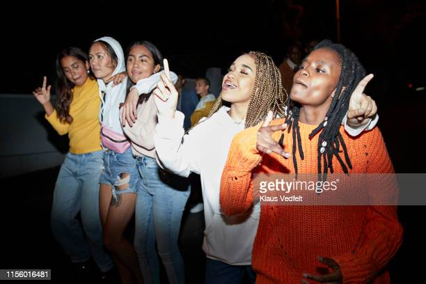 friends singing while dancing on street at night - female friendship stock pictures, royalty-free photos & images