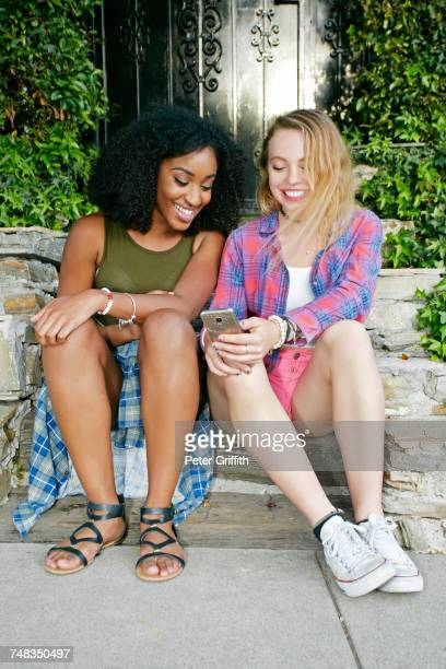 Friends siting on front stoop texting on cell phone