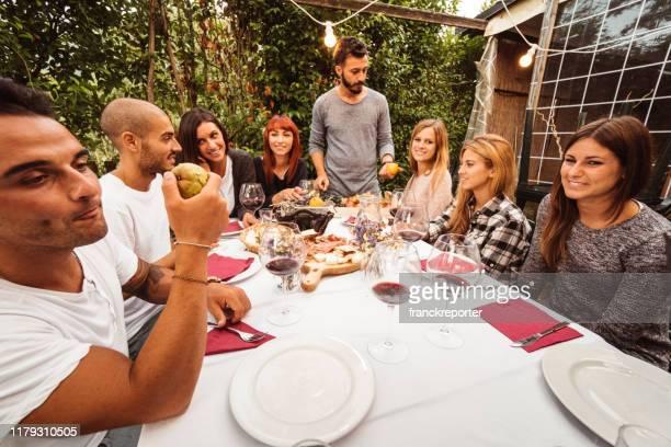 amici sittig al patio tutti insieme - pranzo foto e immagini stock