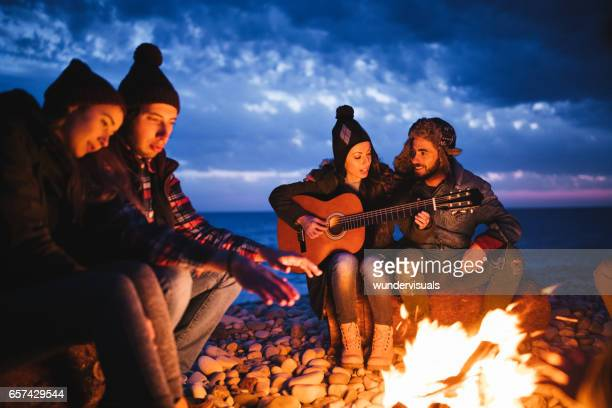 Friends sitting around a campfire at the beach playing guitar