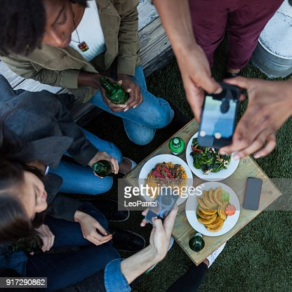 Friends sitting around a table sharing the party on social media