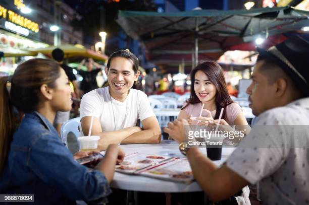 friends sitting around an outdoor restaurant table with drinks - malaysian culture stock pictures, royalty-free photos & images