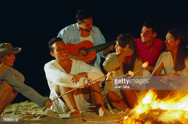 Friends sitting around beach bonfire