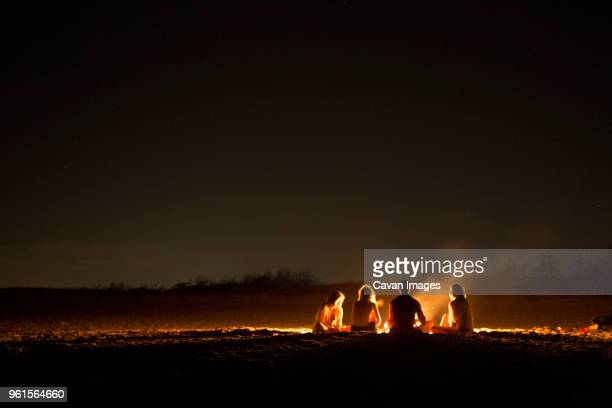 friends sitting around bonfire at beach during night - lagerfeuer stock-fotos und bilder