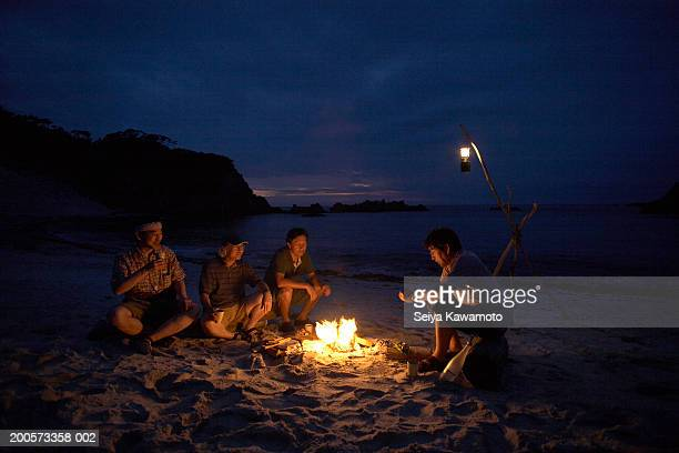 friends sitting around campfire on beach at night - campfire stock pictures, royalty-free photos & images