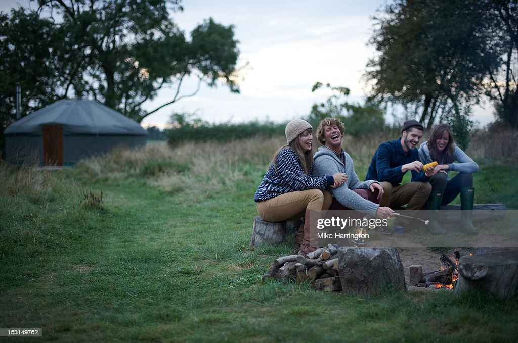 Friends sitting around campfire on glamping trip. : Stock Photo
