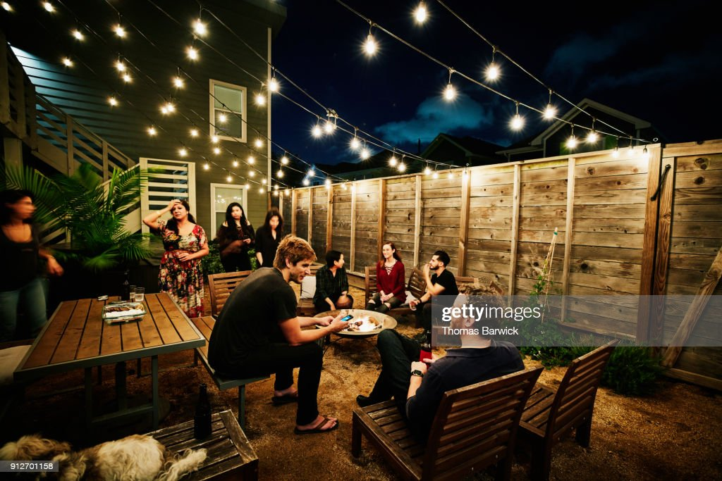Friends sitting around fire during neighborhood backyard party on summer evening : Stock Photo