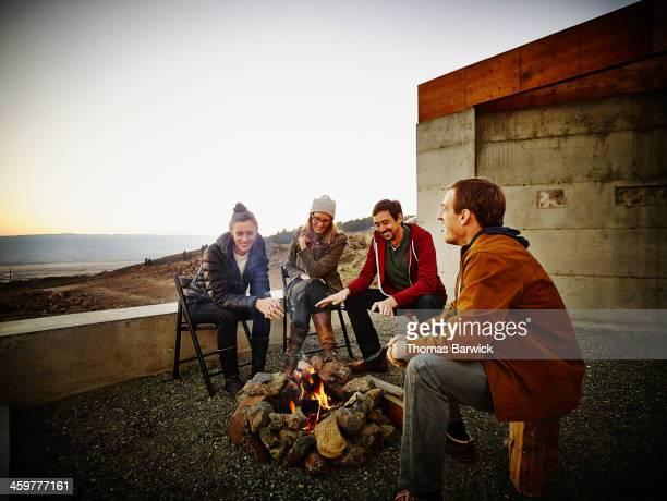 Friends sitting around fire pit at sunset