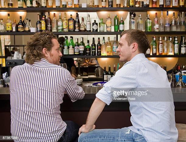 friends sitting at bar drinking - cadrage aux genoux photos et images de collection