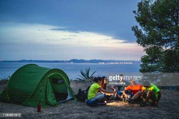 friends sitting at campsite overlooking mediterranean - non urban scene stock pictures, royalty-free photos & images