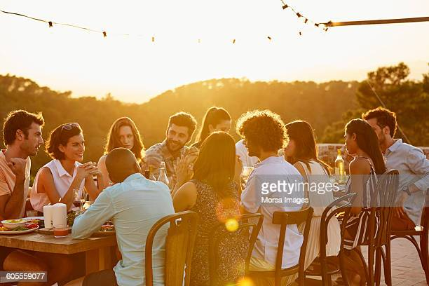 Friends sitting at table during social gathering