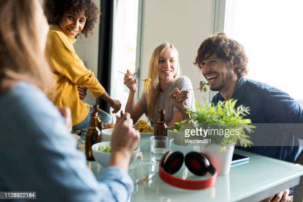 friends sitting at table talking, eating and drinking beer - 30 39 years stock pictures, royalty-free photos & images