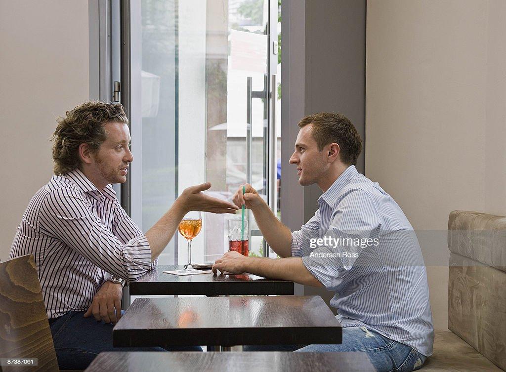 Friends sitting at table talking : Bildbanksbilder