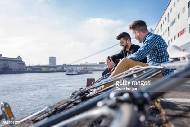 Friends sitting by bicycle in front of canal against clear sky