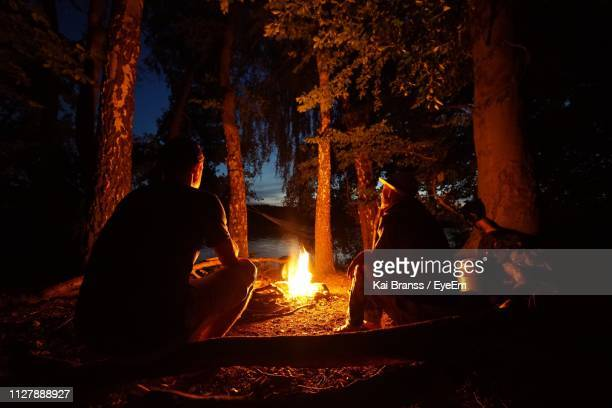 friends sitting by campfire in forest at night - utomhuseld bildbanksfoton och bilder