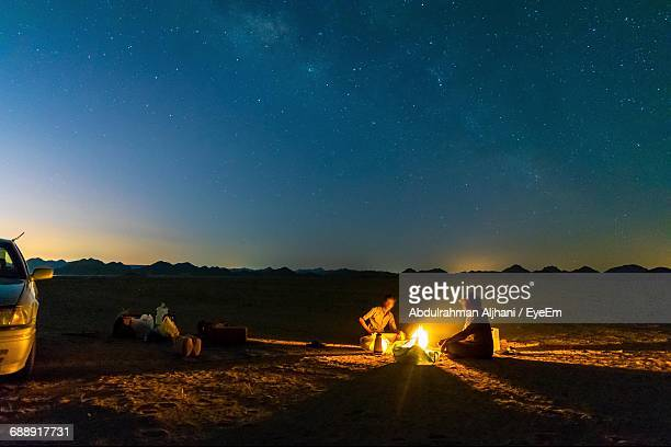 friends sitting by campfire on field at night - camp fire stock photos and pictures