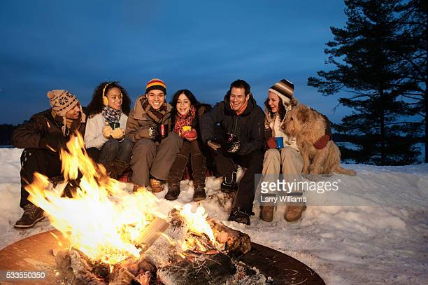 Friends sitting by campfire