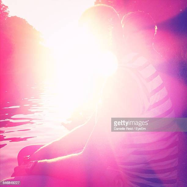 friends sitting by lake against bright sun - danielle reid stock pictures, royalty-free photos & images