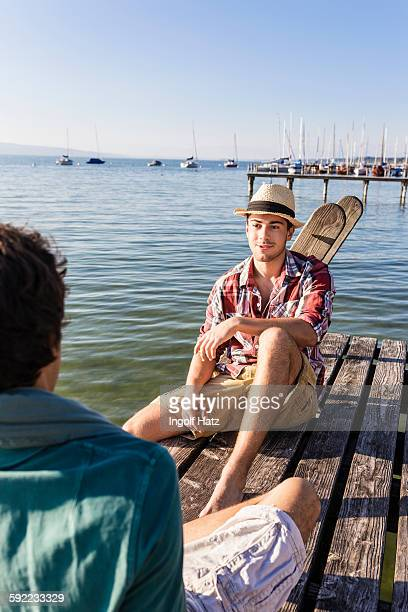 Friends sitting face to face on wood pier next to lake, Schondorf, Ammersee, Bavaria, Germany