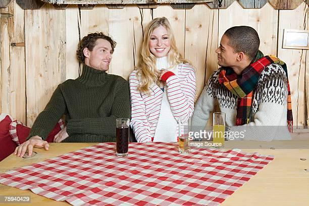 amis assis dans une cabine - femme entre deux hommes photos et images de collection