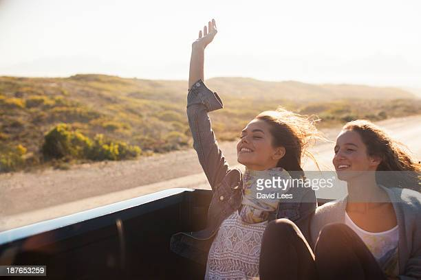Friends sitting in back of truck