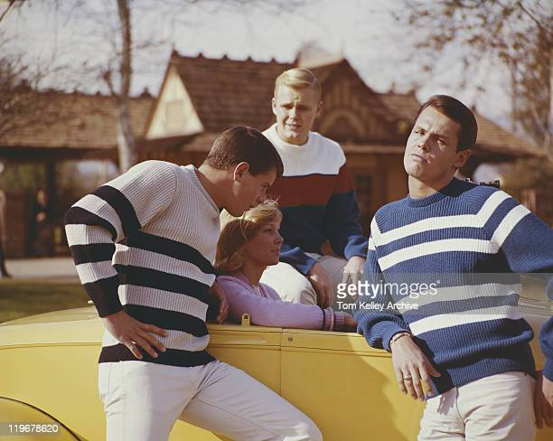 friends sitting in car and standing beside it - 1965 stock pictures, royalty-free photos & images