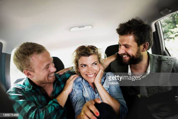 Friends sitting in car, having fun