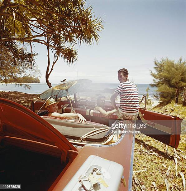 friends sitting in car near beachside - 1962 stockfoto's en -beelden