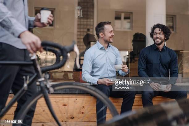 friends sitting in front of coffee shop, talking, drinking coffee - männer über 30 stock-fotos und bilder