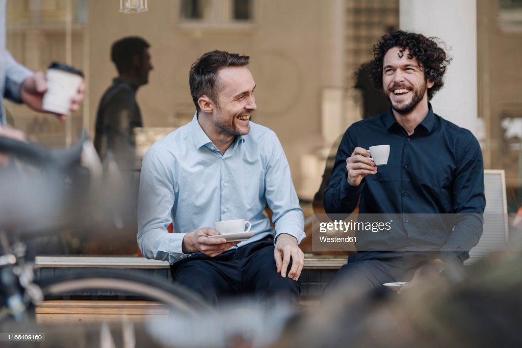Friends sitting in front of coffee shop, talking, drinking coffee : Stock Photo