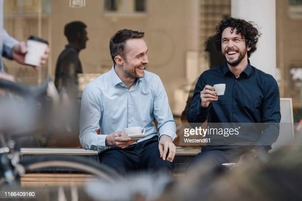 friends sitting in front of coffee shop, talking, drinking coffee - outdoors stock-fotos und bilder