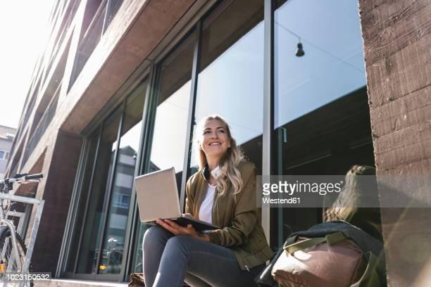 friends sitting in front of window in the city, using laptop - junge frau allein stock-fotos und bilder