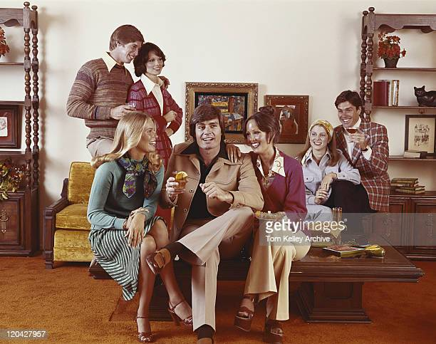 friends sitting in living room having drinks, smiling - 1975 stock pictures, royalty-free photos & images