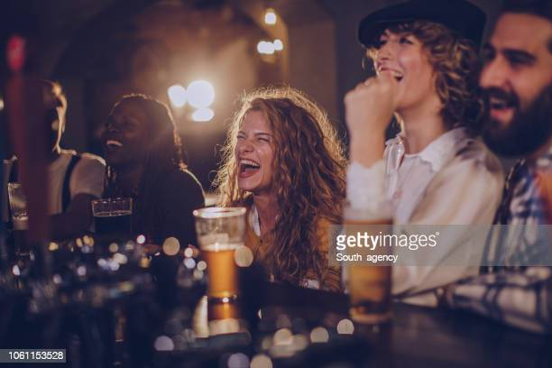 friends sitting in pub - ale stock pictures, royalty-free photos & images