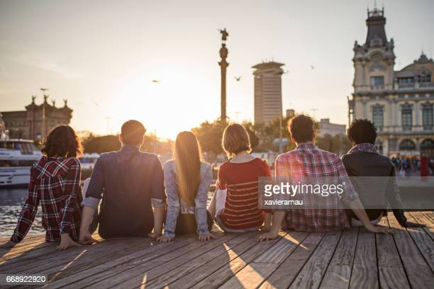 Friends sitting in row on boardwalk