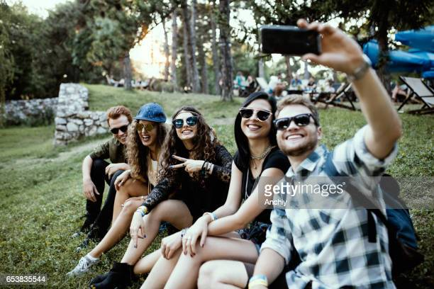 Friends sitting in the grass, having a laugh and taking selfie