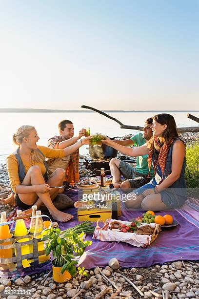Friends sitting next to water having a picnic making a toast, Schondorf, Ammersee, Bavaria, Germany