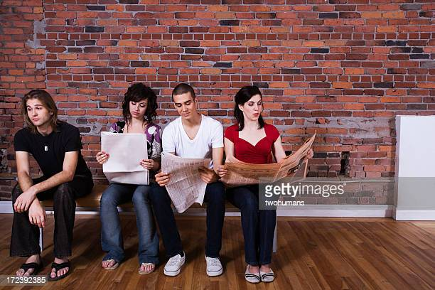 Friends sitting on a bench with three reading a newspaper